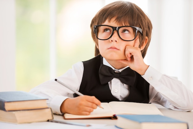 Day dreaming. bored young boy leaning his face on hand and looking away while sitting at the desk