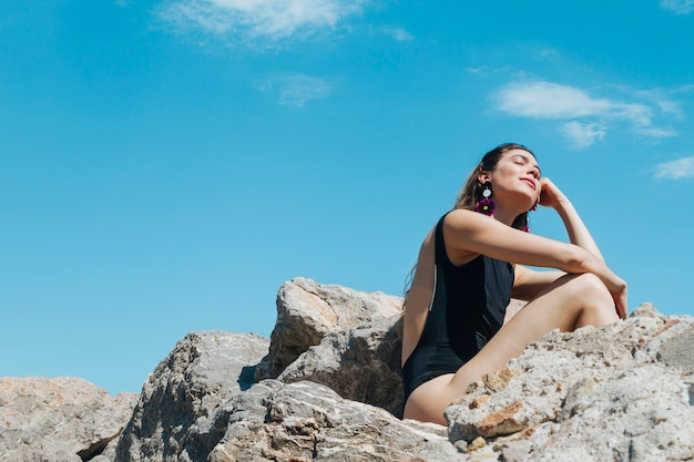 Day dreaming young woman closing her eyes and sitting on rock
