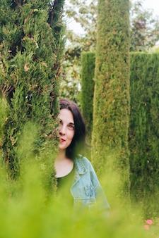 Day dreaming young woman peeking through hedge