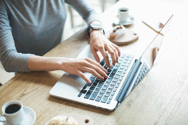 День в кафе. закройте молодой женщины в кафе. студент с вкусным кофейным напитком. она использует ноутбук