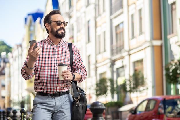 День в городе. позитивный бородатый мужчина идет по улице, попивая кофе