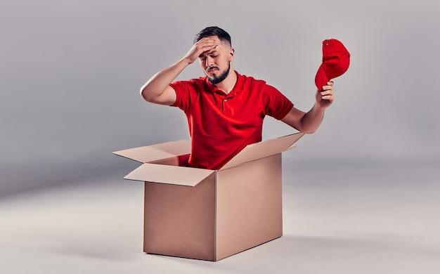 Дневной переезд. доставка товаров из покупок в интернет-магазине. погрузчик или курьер, сидя в коробке и устал на сером фоне.