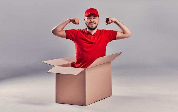 Дневной переезд. доставка товаров из покупок в интернет-магазине. грузчик или курьер сидит в коробке и показывает мышцы на сером фоне.