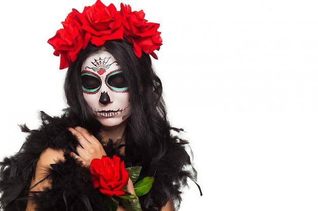 死霊のえじき。ハロウィン。死んだマスク頭蓋骨顔アートとバラの日の若い女性。白で隔離。閉じる。
