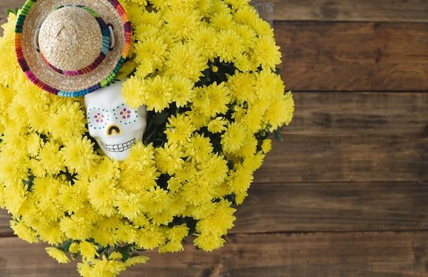 死霊のえじき。木製の背景に頭蓋骨と黄色の花。スペースをコピーします。