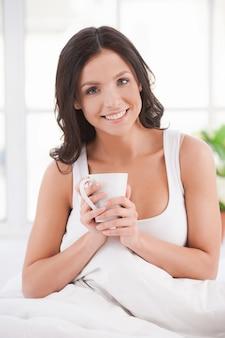 休日の朝。ベッドに座って、毛布で覆われている間カップを保持している魅力的な若い笑顔の女性