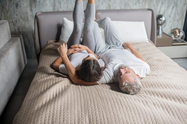 一緒に休日。白髪の男性と黒髪の女性が足を上げてベッドで休んで横たわっている
