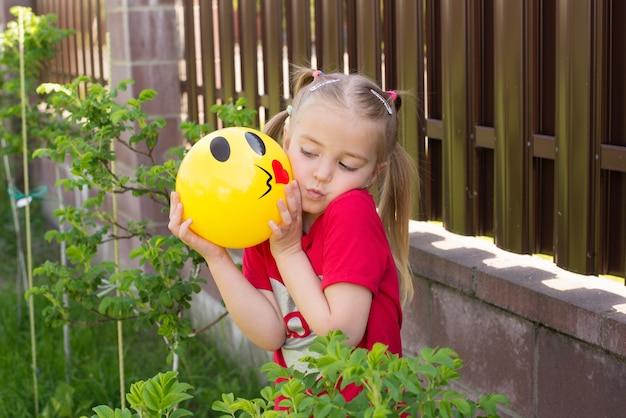 Day of the smile emoji girl child holding a ball in her hands playing in the yard in the summer walking