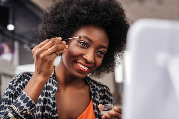 Day in a studio. smiling dark-skinned woman in an orange top looking involved while trying new eyebrows shape