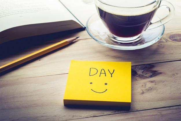 朝の机のテーブルにメモ帳、メモ帳、コーヒーカップと日中のテキスト