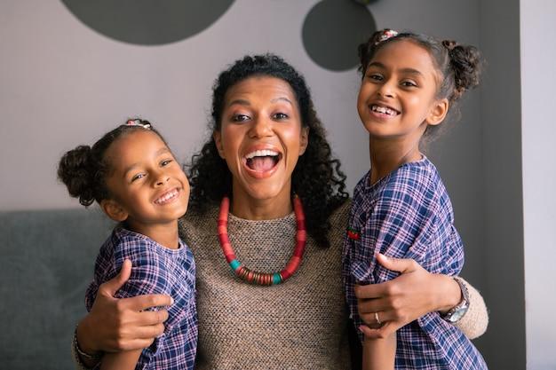 День с дочерьми. кудрявая темноволосая красивая женщина чувствует себя чрезмерно эмоциональной, проводя день с дочерьми