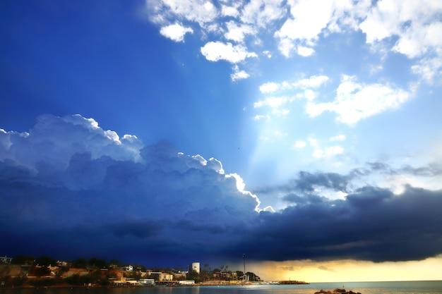 海の嵐の後の夜明け、太陽の光がビーチと灯台を照らします