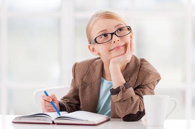 Мечтатель. задумчивая маленькая девочка в очках и формальной одежде сидит за столом и держится за руку