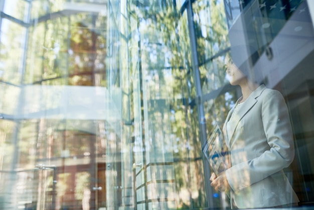 Daydreaming businesswoman enjoying view behind window