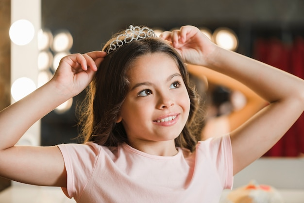 Daydreaming girl holding crown on her head looking away