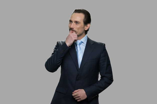 灰色の背景に空想の成熟したビジネスマン。あごに手をつないで物思いにふける表情でハンサムなビジネスマン。