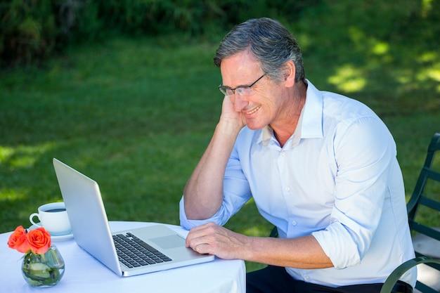 Вскользь бизнесмен используя компьтер-книжку daydreaming