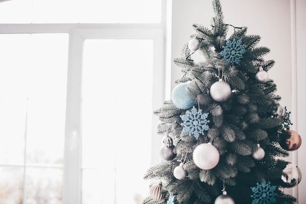 Дневной свет в комнате. рождественская елка с украшением стоит в белом пространстве. подготовка к празднику.