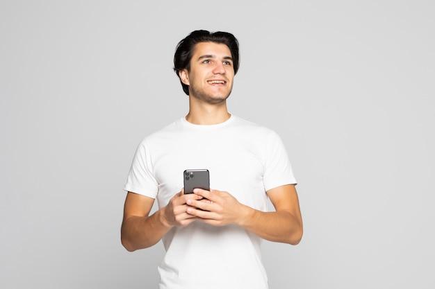 Ritratto alla luce del giorno di giovane uomo caucasico europeo isolato su grigio che indossa bianco con smartphone