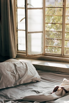 Daylight shining through an unmade bed