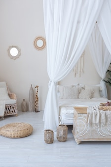 Daylight through a huge panoramic window illuminates the cozy oriental interior of the room in beige colors with wicker furniture and authentic elements