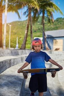 주간 오락 및 스포츠 취미. 야외에서 스케이트보드를 들고 공원의 계단을 걸어가는 모자를 쓴 멋진 옷을 입은 소년.