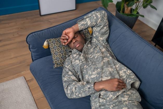 낮잠. 집에서 소파에 누워 이마에 손을 만지고 닫힌 눈을 가진 위장에 젊은 성인 검은 피부 남자