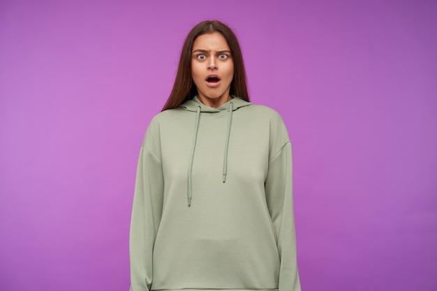 Ошеломленная молодая зеленоглазая шатенка с естественным макияжем удивленно смотрит вперед с открытым ртом, стоя у фиолетовой стены с опущенными руками