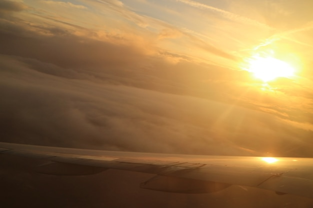 Dazzling sun on the cloudscape as seen from the plane window