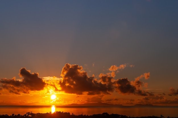 Dazzling sunrise behind ishigaki island colorful clouds sunbeams top view seen from iriomote island