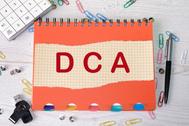 Dca text on a piece of paper over a notebook, with clips around and a calculator on a desk