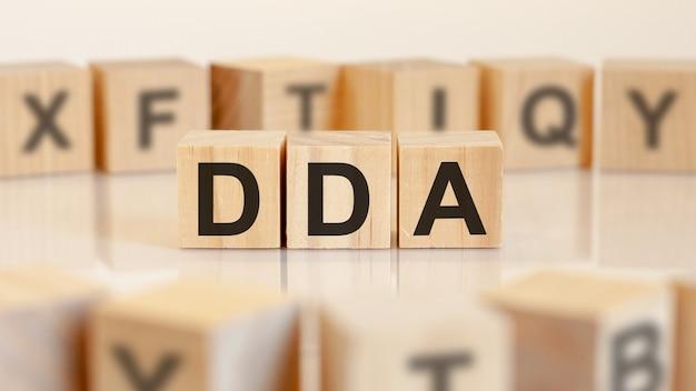 Dda-문자가있는 나무 블록의 약어, doha development agenda 또는 약어 dda 개념으로 비즈니스 수행, 주위에 임의의 문자, 노란색 배경