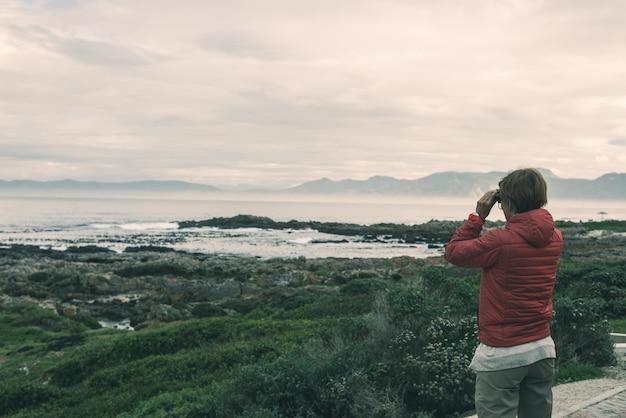 Турист смотря с биноклем на скалистой береговой линии на de kelders, южной африке, известной для наблюдать кита.