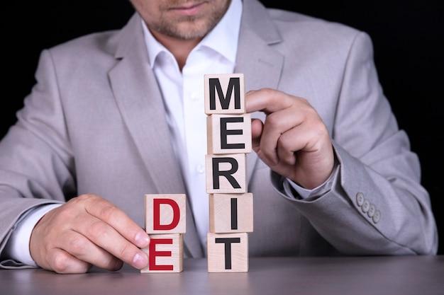 De merit、単語は木製の立方体に書かれ、灰色のスーツを着たビジネスマンを背景にブロックします。