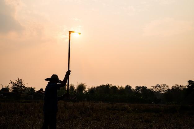農業農家の生活概念:労働者または踏deを保持している庭師の黒いシルエットは夕日の光で土を掘る