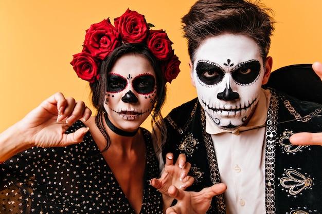 黄色の壁に不気味なポーズで死んだカップル。ハロウィーンを祝うゾンビの服装の素晴らしい男たち。