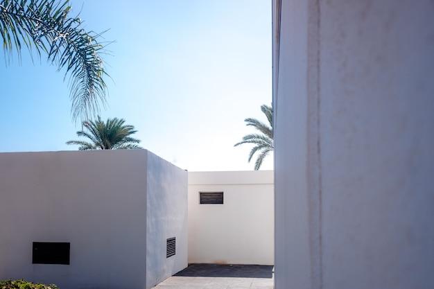 Тупик с белыми стенами на летнем пляже, уединенная солнечная улица.