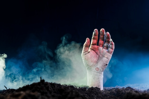 Dead hand protruding of ground in fog