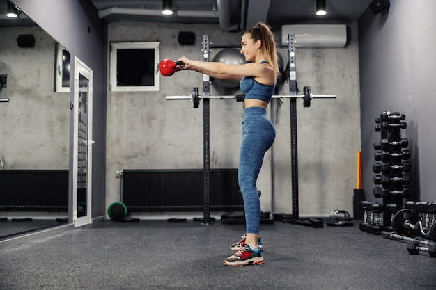 Dead lift kettle bells to burn the muscles of the buttocks and legs. portrait of a beautiful woman in sportswear and in good physical shape lifting weights in a dark atmosphere indoor gym