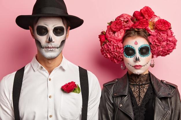 死んだ不気味なカップルは一緒にハロウィーンを祝い、コスチュームパーティーを開催し、伝統的なメキシコの服装、鮮やかなメイク、赤い花の花輪を着て、スタジオでポーズをとり、肩を並べて立ちます。死者の日