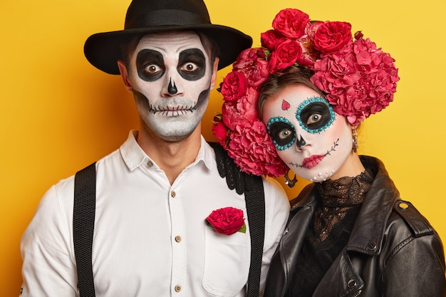 Dead woman and man wears skull makeup, painted for halloween, look at camera surprisingly, dressed in black and white outfit for all saint day, isolated over yellow background.