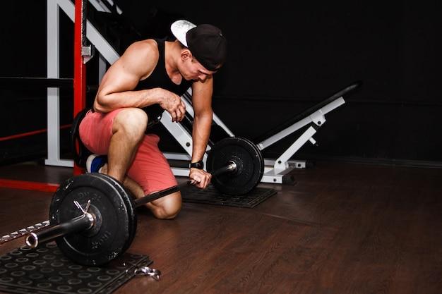 Deadlift. sports man lifting barbell row at gym
