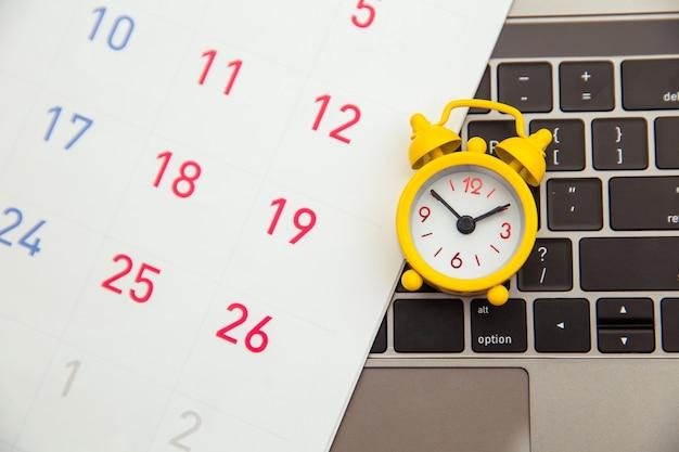 締め切りのコンセプト。ノートパソコンと目覚まし時計、黄色の背景に月間カレンダー。時間がなくなっています。
