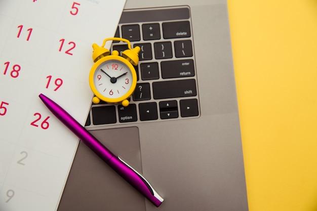 締め切りのコンセプト。ノートパソコンと黄色の目覚まし時計、黄色の背景に月間カレンダー。時間がなくなっています。