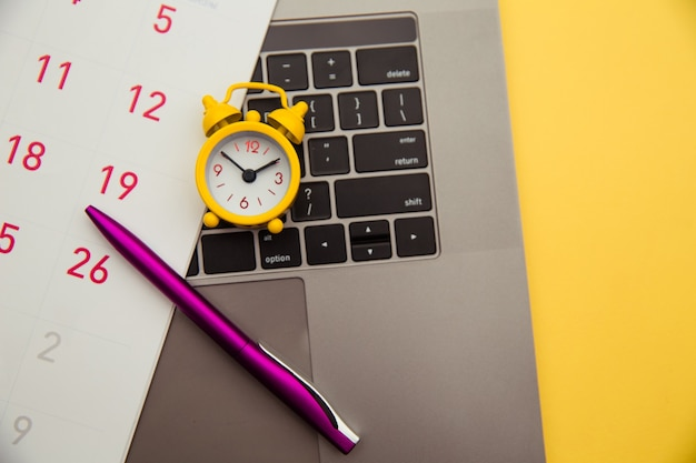 Deadline concept. laptop and yellow alarm clock, monthly calendar on yellow background. time is running away.
