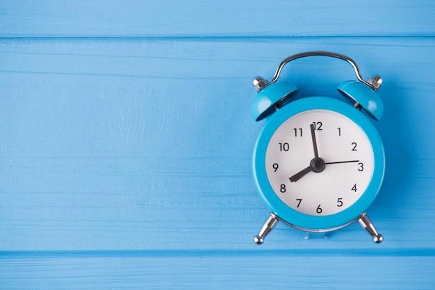 締め切りのコンセプト。コピースペースと青い木製の背景で隔離の青い時計の俯瞰図のクローズアップ写真の上の上