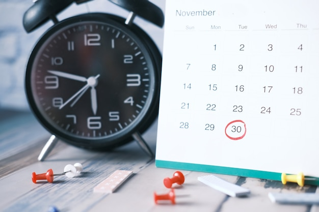 Deadline concept with calendar and alarm clock on table