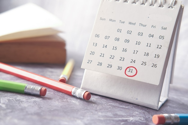 Deadline concept with red mark on calendar date with book and pencils on table