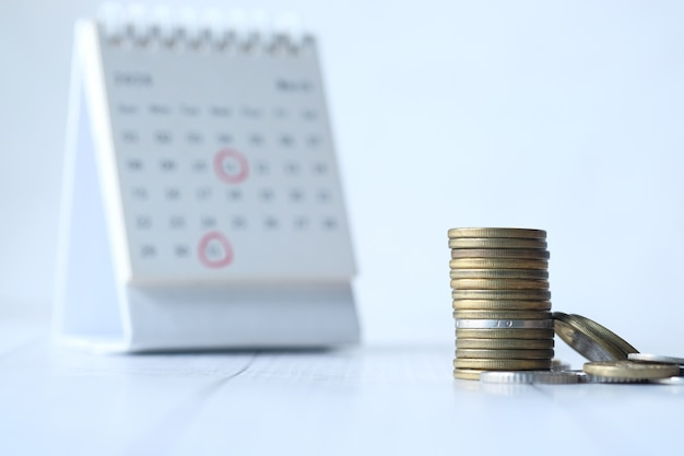 Deadline concept with stack of coins and calendar
