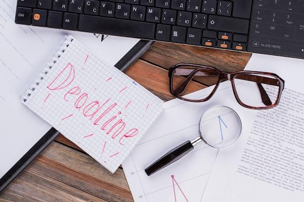 Крайний срок на блокноте и различных деловых бумагах на коричневом фоне